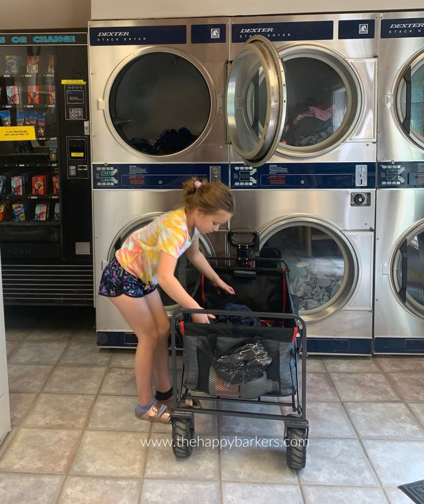 Ellie loading wash in the double stacked washer in the campground laundry